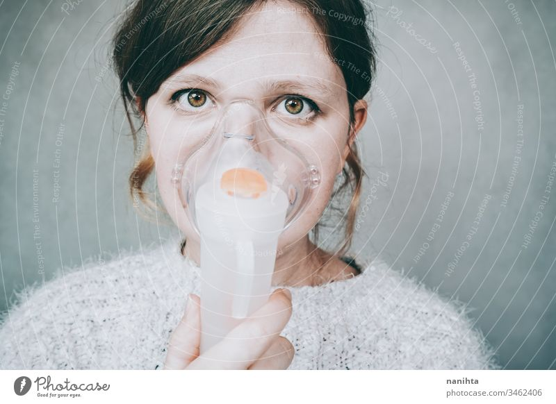 Young woman using a breathing mask covid 19 coronavirus pandemic illness oxygen infected contagious infection allergy asthma health healthy breathing medical