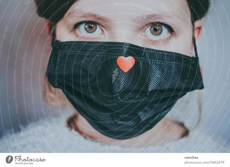 Young woman wearing a mask with a red heart on it covid 19 coronavirus breath pandemic illness hope love help solidarity empathy care infected contagious