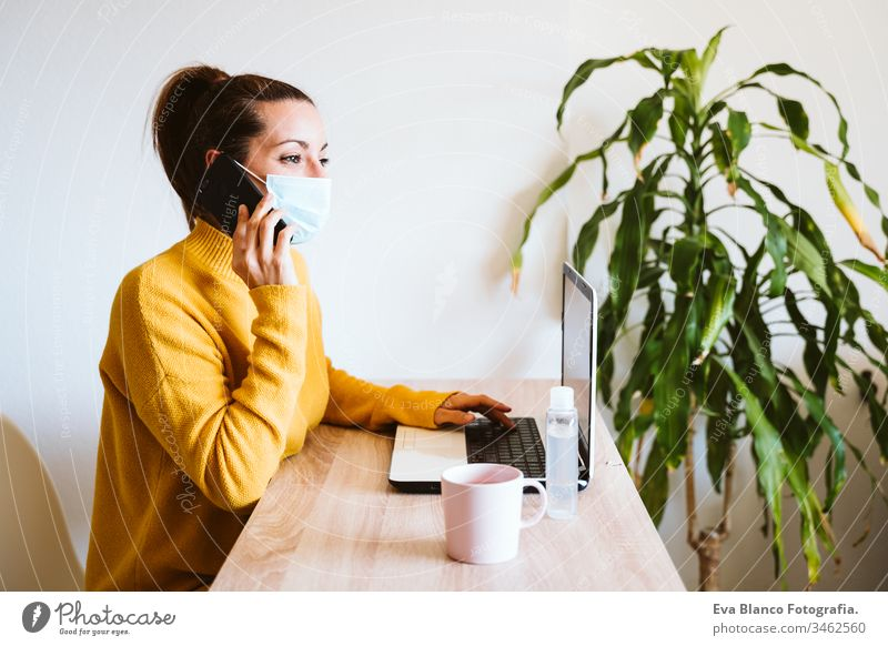 young woman working on laptop at home, wearing protective mask. work from home, stay safe during coronavirus covid-2019 concpt pandemic stay home dog pet