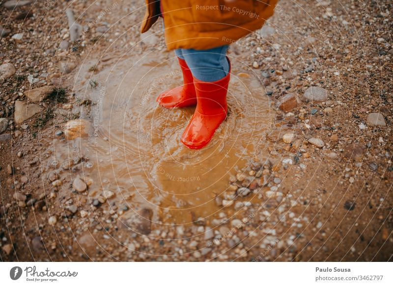 Feet of child in red rubber boots over a puddle Red Rubber boots Boots Rain Child Wet Exterior shot Weather Colour photo Puddle Human being Joy Water Dirty
