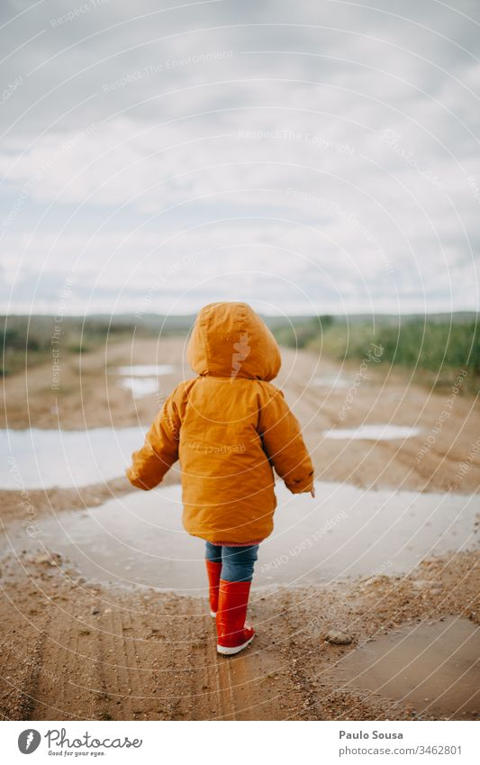 Rearview child walking in a puddle with orange jacket Orange Rubber boots Red Puddle Wet Exterior shot Colour photo Rain Human being Joy Child Water Playing