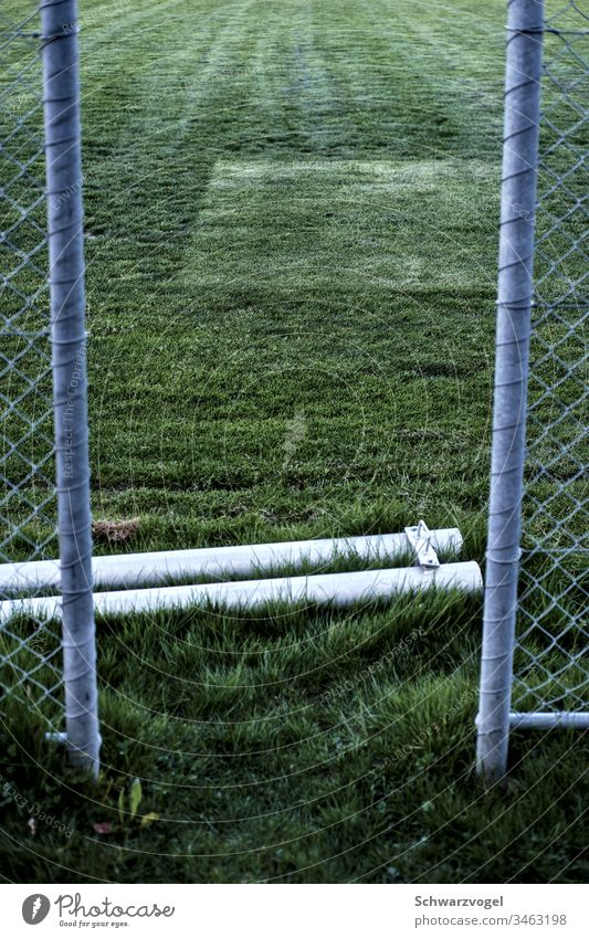 Access to a grass field Sports facility Lawn Lanes & trails Fence Gap in the fence Pole Pattern Green Tracks Meadow Grass Sporting grounds soccer field
