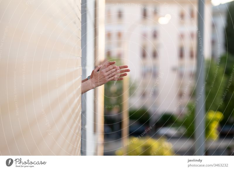 Woman clapping in the window in support of people who fight against the coronavirus epidemic balcony woman girl health building global you infection house