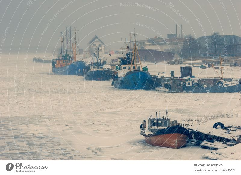Fishing boats in the ice of a frozen bay baltic beach blue business cargo city coast cold commercial covered december europe european february fishing freight