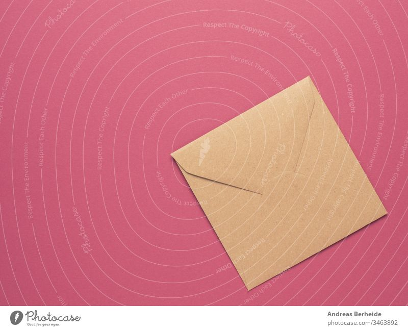 An envelope made from recycled paper on a red background with copy space isolated letter mail blank white post message communication correspondence card open