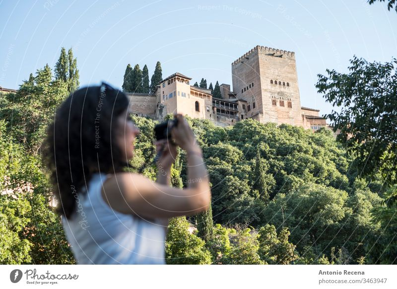 Woman tourist taking pictures in La Alhambra, Granada, Spain woman la alhambra camera tourism blurred person one person women outdoors granada andalusia spain