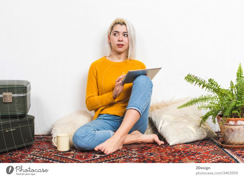 Young woman using tablet computer while sitting on floor at home. 1 young beautiful adult happy technology people cyberspace female digital person girl white