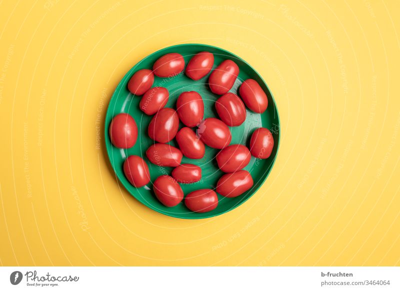 Date tomatoes in a green plastic plate tomato with dates Plate Green Yellow Middle Vegetable Nutrition Red Deserted Healthy Eating Food photograph Tomato