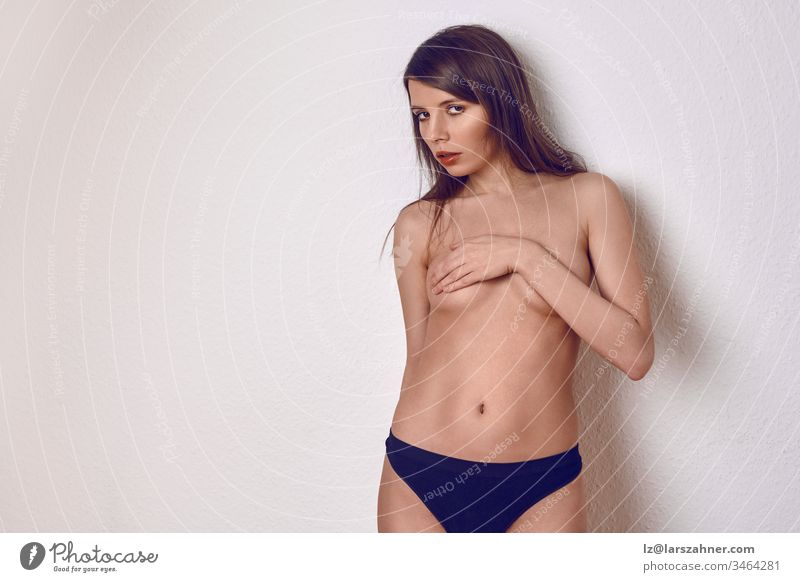 Topless sexy young brunette woman in blue panties, covering her breast with one hand, stands on a light background in the studio and looks into the camera with a seductive look. Front portrait with copy room