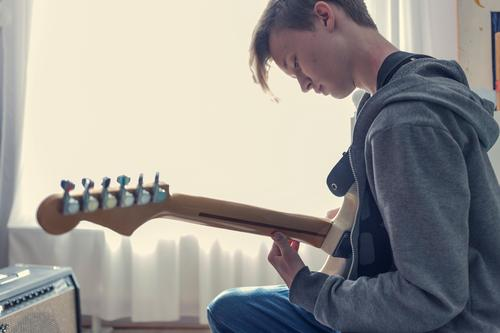 Male teenager plays an electric guitar in his room. Guitar Electric guitar Fantasy Sunlight Youth culture Window Room Quarantine covid-19 Virus Creativity