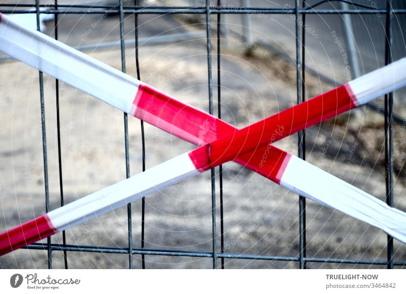 Not an X for a U but a warning made of red and white fluttering tape that points to a grid of thin wire mesh and says: Stop! Here we cannot continue because of a construction site.