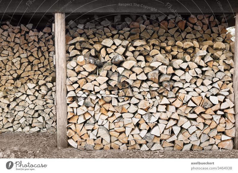 stacked firewood in wood shed fire wood woodpile chopped natural lumber timber material background tree cut energy forest log industry wooden outdoors fuel