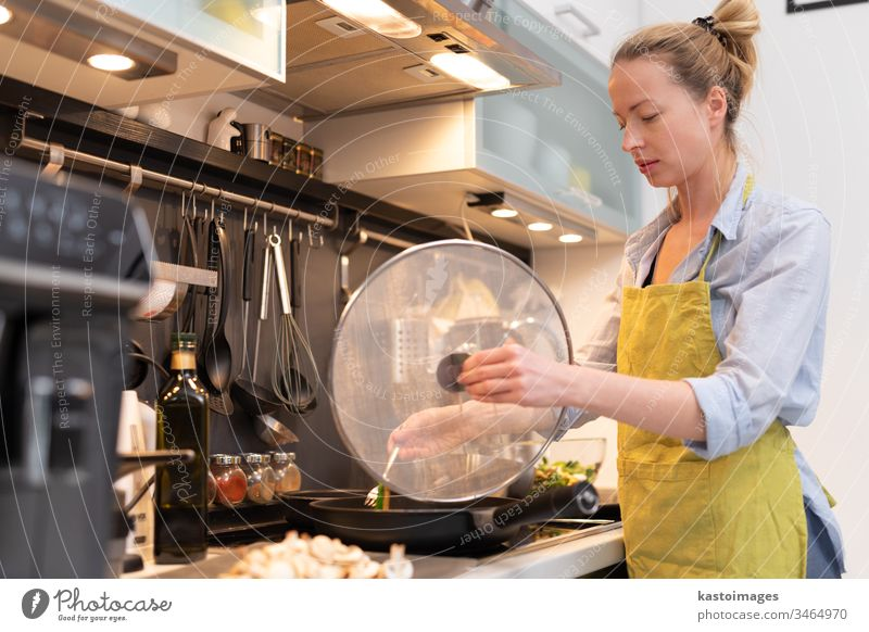 Stay at home housewife woman cooking in kitchen, stir frying dish in a saucepan, preparing food for family dinner. young healthy meal person vegetable female