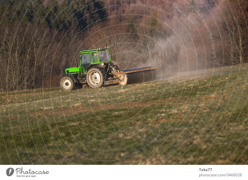 a tractor on a meadow in the evening green tractor modern tractor agricultural agriculture business country countryside cultivate cultivation environment