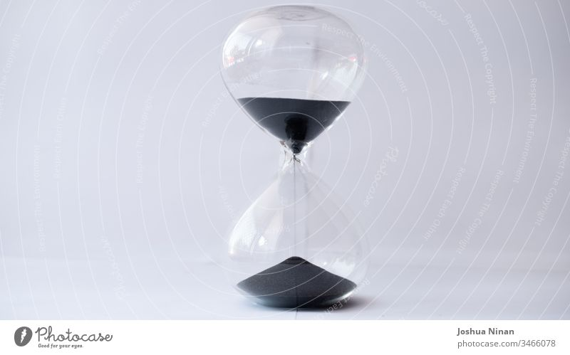 Hourglass with black sand running out background black sand hourglass clock concept countdown deadline egg timer flowing future measure of time measurement