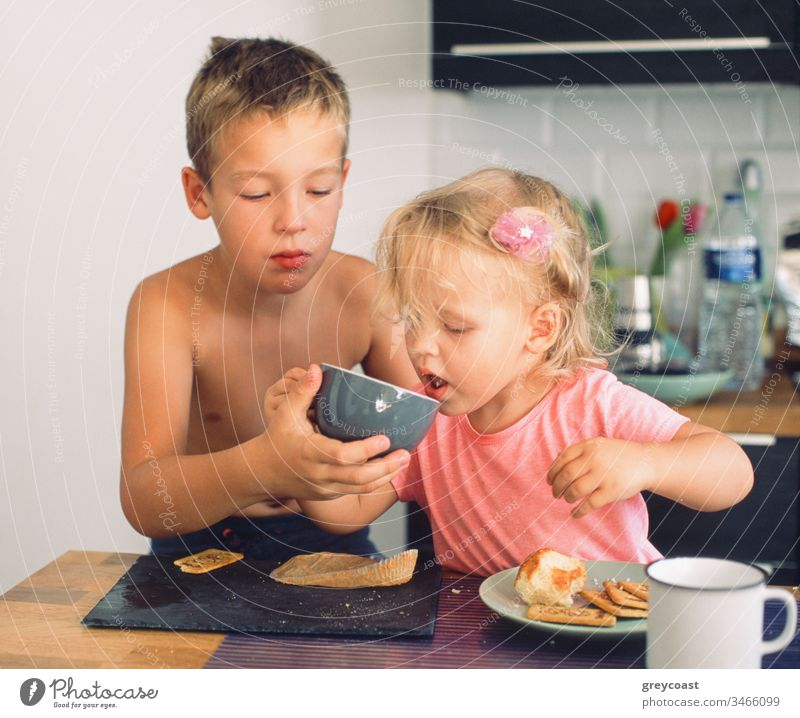 Elder brother taking care of junior sister and helping her drink from the cup during breakfast. Everyday morning moments children tea meal take care siblings