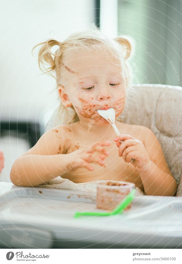It does not matter how dirty your face is when it is so yummy. Little girl eating sitting in highchair kid messy eater breakfast child toddler portrait baby