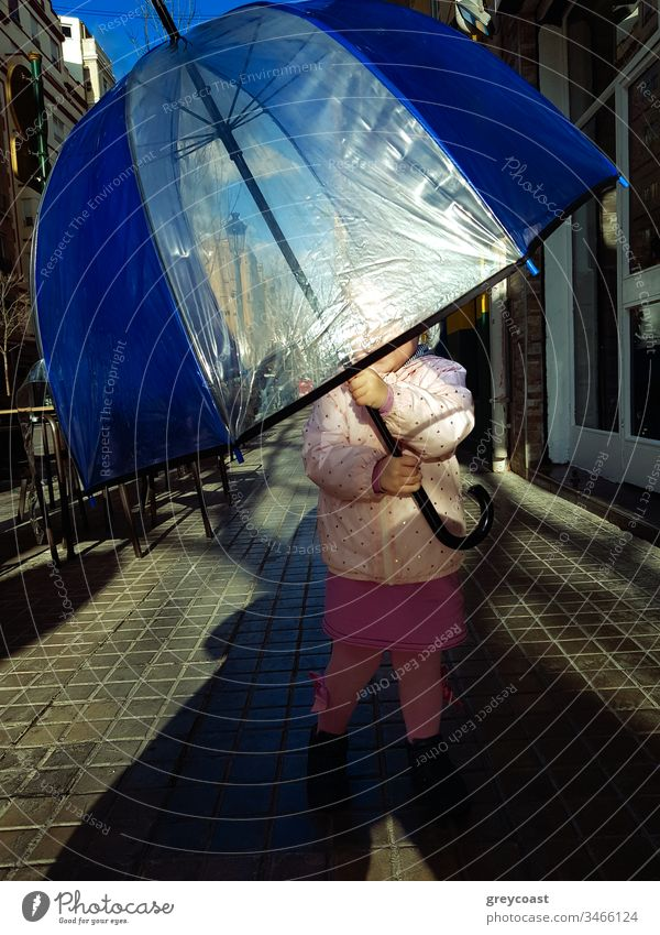 Little girl with big umbrella against the sun in the street. Child loves to hide under child kid toddler autumn outside fall lady playful weather city people