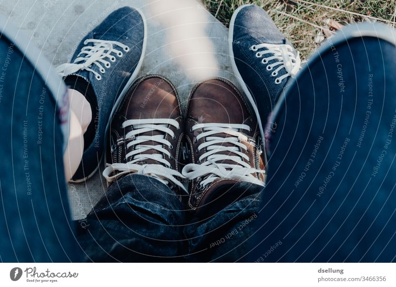 Young couple shows their feet relaxed in modern shoes and form an inspiring formation Bird's-eye view Deep depth of field Sunlight Shadow Light Day Deserted