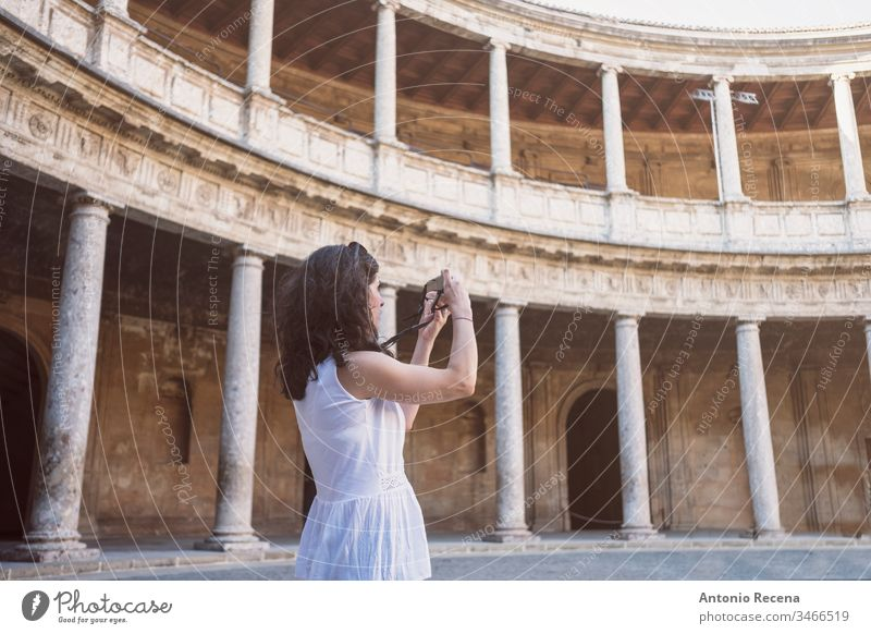 Tourist woman taking pictures to La Alhambra in sunny day. Carlos V palace city view architecture built structure building travel travel destination landmark
