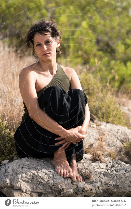 A vertical shot of a beautiful female Latina sitting on a rock by the bush woman beauty white girl young nature pretty portrait adult background attractive