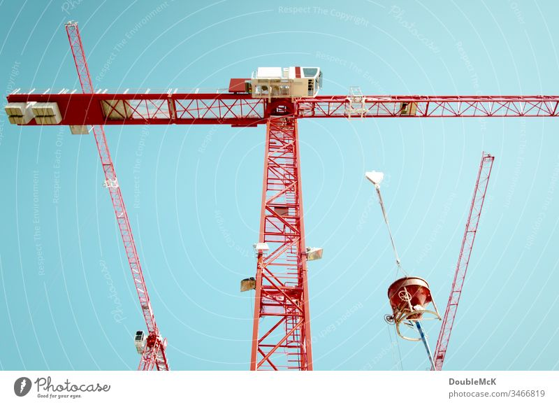 Three red cranes with a concrete mixer in front of a blue sky Crane Construction site Exterior shot Sky Blue Colour photo Work and employment Day Steel Tall