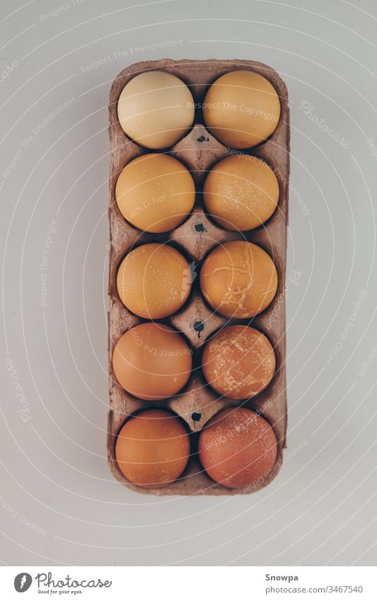 Different shades of brown eggs in a carton egg box. protection cardboard groceries nature organic chicken package food protein animal healthy paper easter