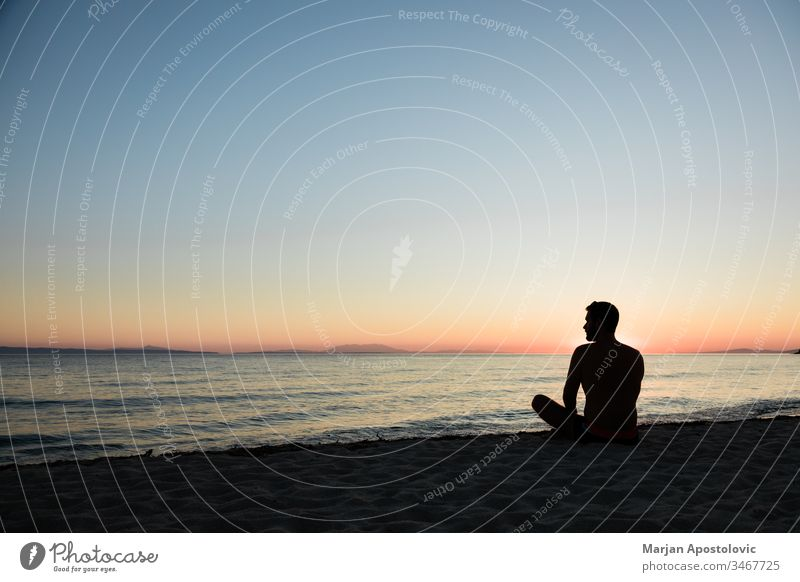 Young man enjoying sunset on the beach adult adventure alone beautiful calm coast dawn dusk evening freedom harmony holiday horizon island landscape lifestyle