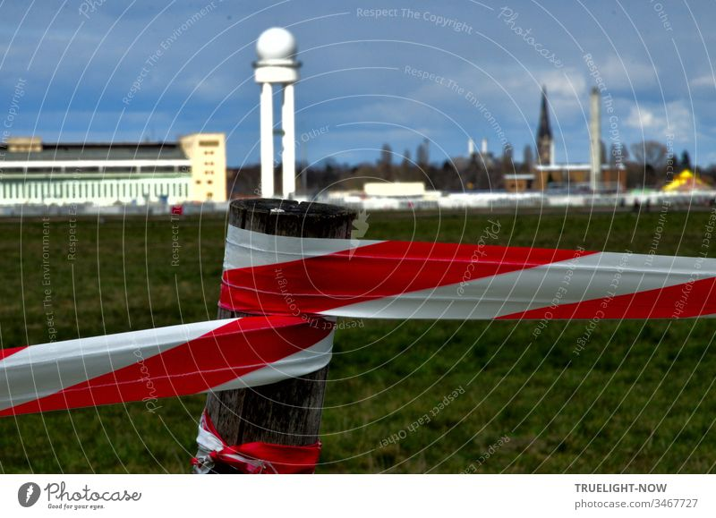 Corona Thoughts | The Tempelhofer Feld leisure area is marked with red and white barrier tape and in the background, against a dark cloudy sky, the striking airport building glows in the sunlight