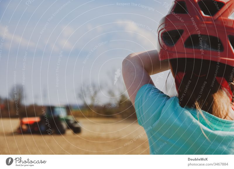 Girl with red bicycle helmet watches tractor in the field Träcker Tractor bulldog Agriculture Field Colour photo Exterior shot Work and employment Nature