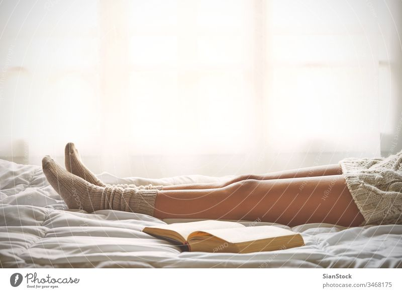 Soft photo of woman legs on the bed with old book next her read reading window view lazy sunday winter coffee cup tea morning girl home relax socks beautiful