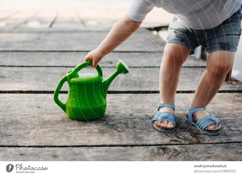 A small girl is playing with a watering can of a wooden bridge. Spring and summer. Gardening. green watering can baby little child cute garden background white