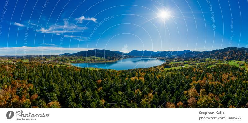 Fantastic panoramic view over the bavarian lake Tegernsee in autumn with fall colors, shot by a drone. mountains nature water sun aerial travel tourism total