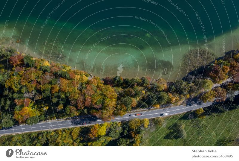 Top View of a beach nearby trees and a road with driving cars in autumn. water late summer nature sea landscape bay shore coast tropical sand island view ocean