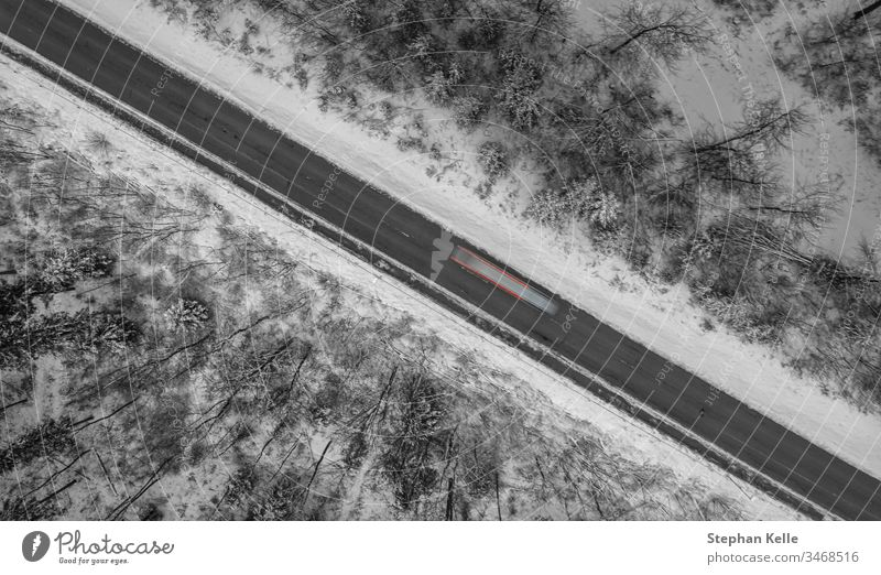 Aerial view on a winter street framed by snow, a car is passing by as a long exposure shot. road diagonal line lights schwaebische alb albstadt living drone