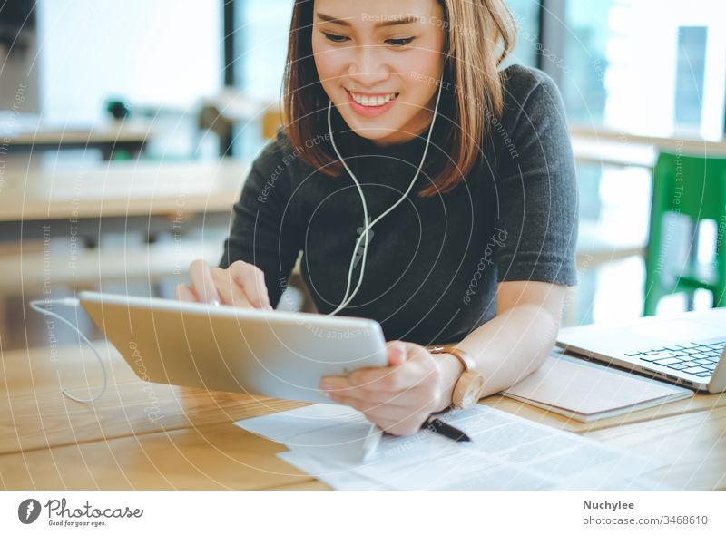 Young smiling asian businesswoman listening music and using tablet in office or cafe, lifestyle and business concept casual cheerful city communication computer