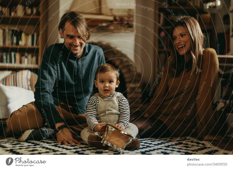 Young happy couple staying at home with their baby son sitting on the living room floor. lovely happiness man woman cheerful carpet smile growth caring boy