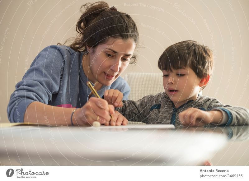 Mother helps little son to do homework at home mother children education woman family mother's day love write taught 4s 30s 40s lifestyle casual home indoor