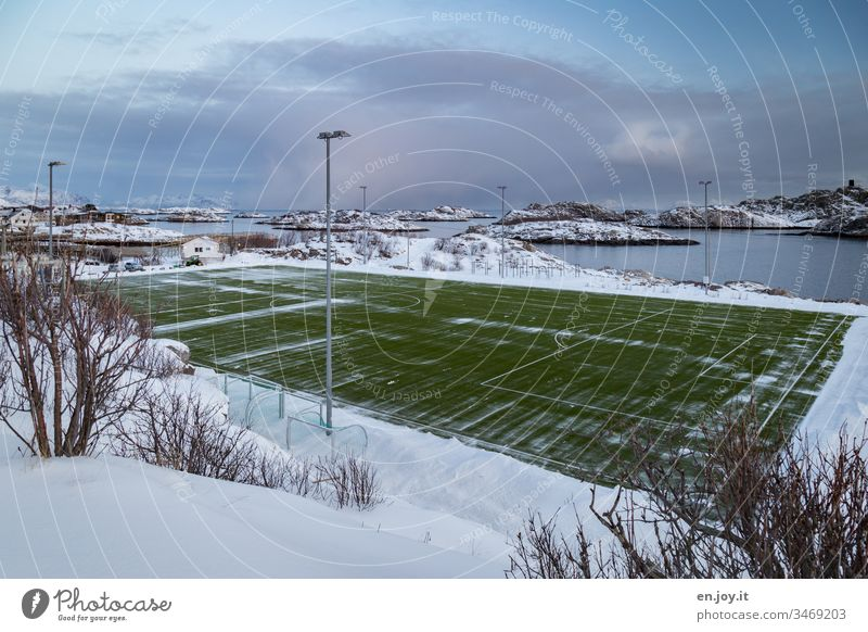 green football field on an island in the sea in a snowy landscape Henningsvær Lofotes Norway Scandinavia Island Winter soccer field Snow Sporting grounds