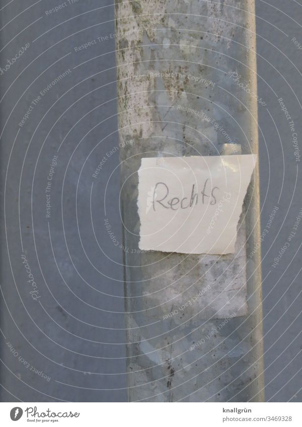 "Paper snippets with the inscription ""Rechts"" glued to a lamppost with two pieces of adhesive film Piece of paper Lamp post Word Letters (alphabet) torn down"