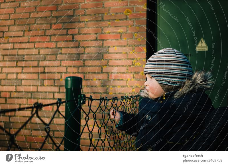 little boy looks into the distance Toddler Boy (child) Observe Wire netting fence look see search. look look look afar look away wander far and wide