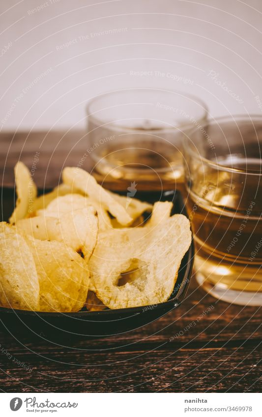Still life of pale ale beer and chips party food food and drink alcoholic drink potatoes aperitif appetizer snacks date two glass wood wooden background cuisine