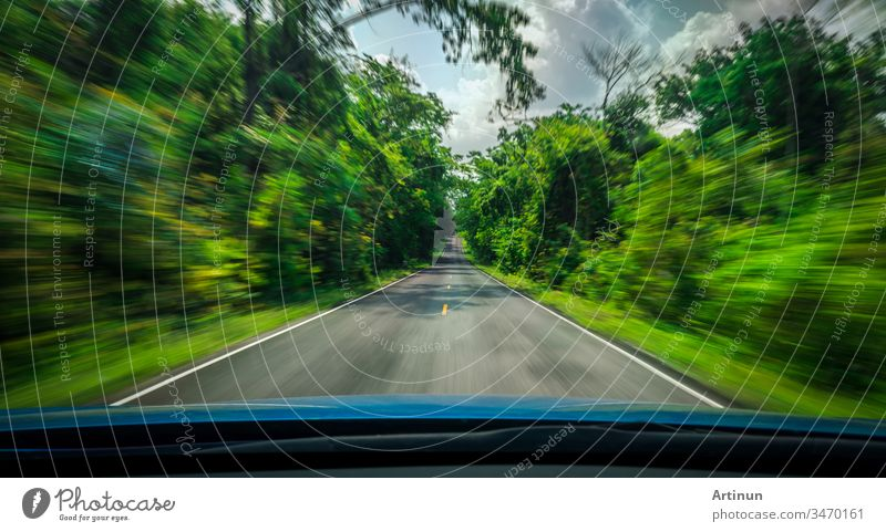 View from front of blue car on asphalt road and speed motion blur on highway in summer with green trees forest at countryside abstract art background blurred