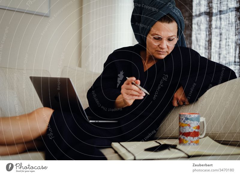 Beautiful woman in a bathrobe sitting on the couch in the home office with laptop, pen and notebook Woman Stayhome Bathrobe Cup Coffee cup Notebook Sit labour
