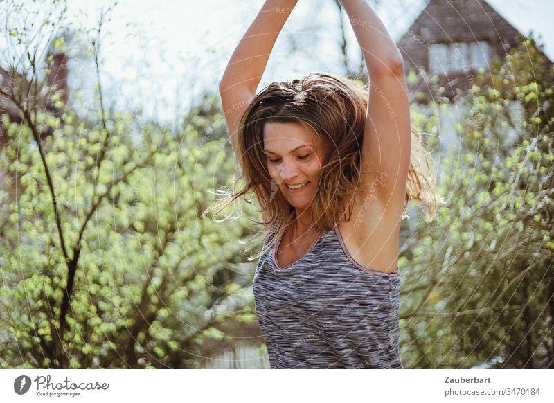 Beautiful woman jumps with raised arms in springlike garden Woman green Jump Sports Joy Joie de vivre (Vitality) already Exterior shot luck Movement Feminine
