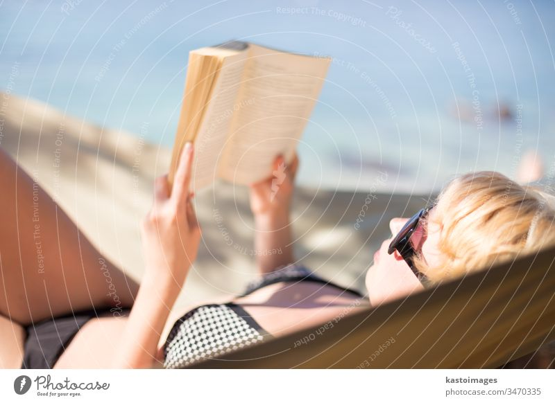 Lady reading book in a hammock. adorable attractive beach beautiful beauty bikini blonde blue body caucasian closeup education face female girl happy healthy
