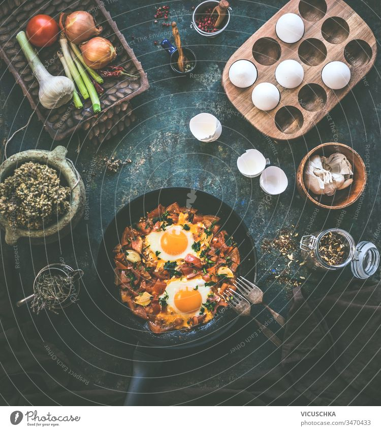 Tasty fried eggs in tomato sauce in black pan with fork on rustic background. Top view. Shakshuka breakfast. Ingredients. Cooking. Healthy food eating tasty