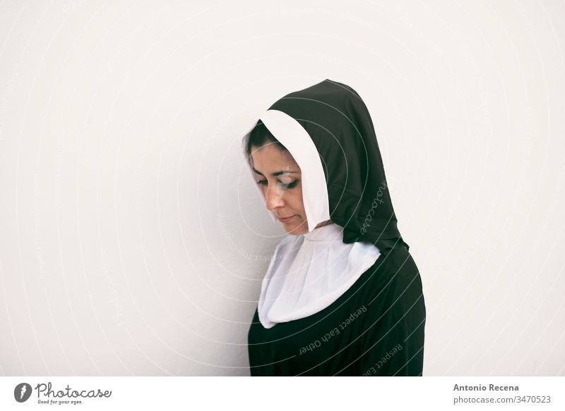 nun on white background looking down serious woman religion habit catholicism 30s 40s costume cliche pretty attractive isolated one person people feminine