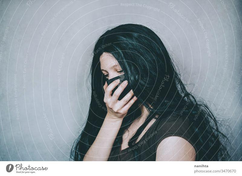 Sad woman wearing a black face mask covid covid 19 corona virus surgery mask protective protection illness infection contagious hand sorrow grief sad sadness