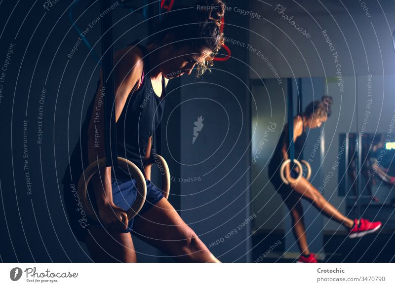 Woman working out with effort expression with rhythmic gymnastic rings in a gym tired training artistic body aerobics athlete competition exercise gymnastics